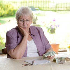female senior is calculating her little budget